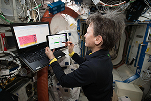 Image of an astronaut using NASA's Playbook tool to schedule her mission activities.