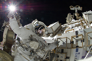 Image of an astronaut on a space walk performaing maintenance activities to a vehicle.